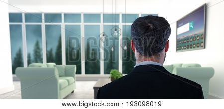 Businessman pretending to standing against invisible screen against blue sofas on floor in modern living room