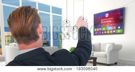 Rear view of young businessman in suit pointing against white sofas in modern living room