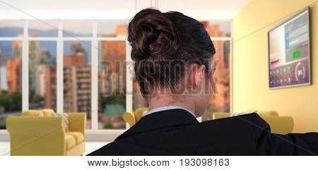 Rear view of businesswoman using digital screen against computer generated interior of modern living room