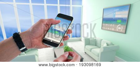 Close-up of man holding mobile phone against computer graphic interior of modern living room