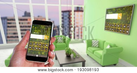 Close-up of hand holding mobile against composite image of modern living room