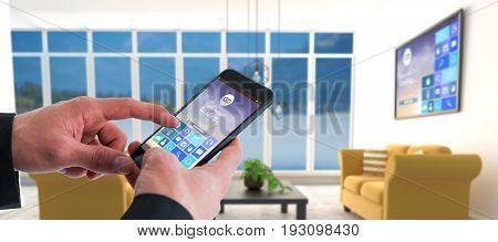 Businessman using smart phone against yellow sofas on floor in modern living room
