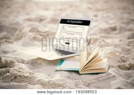 Digitally generated image of Job Application  against open book and laptop on sand at beach