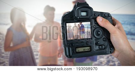 Cropped hand of photographer holding camera  against smiling friends standing by barbecue