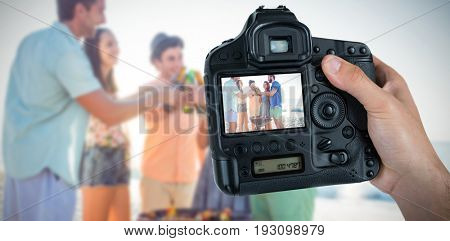 Cropped hand of photographer holding camera  against happy friends by barbecue holding beer bottles