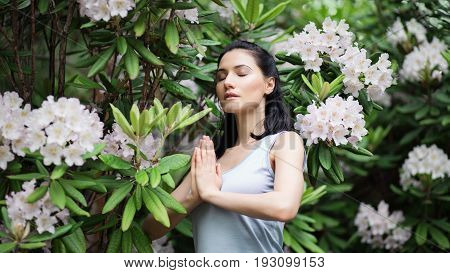 Portrait of beautiful woman in greeb leaves and blooming flowers. Shallow depth of field