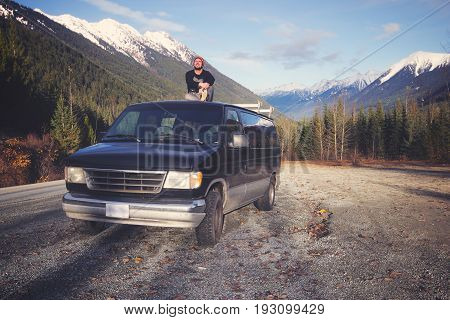 Young man sitting on top of his car in beautiful mountain scenery - concept of inspiration, traveling, freedom, adventure