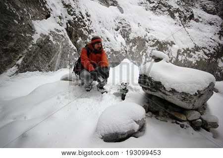 Young man making a hot coffee in mountains back country during freezing a snowy day - concept of camping, traveling, adventure