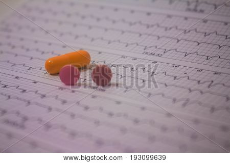 Blurred electrocardiogram strip and three large colored pills out of focus.