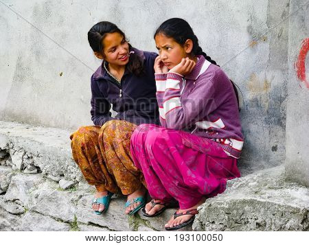 VASISHTA VILLAGE CITY OF MANALY STATE HIMACHAL PRADESH INDIA - APRIL 18 2014: Two Indian girls are sitting at the source in a small village in the Himalayas in the north of the state Himachal Pradesh.