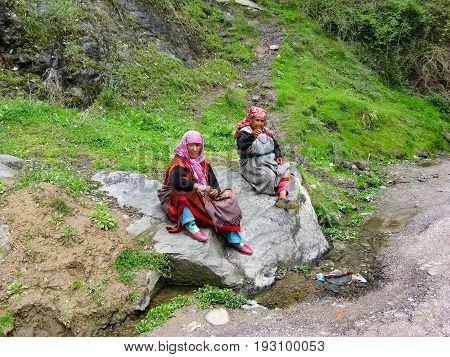 VILLAGE NAGGAR VALLEY KULLU STATE HIMACHAL PRADESH INDIA - APRIL 19 2014: Two grandmothers sit on a stone in small village in Himalayas in north of state Himachal Pradesh.