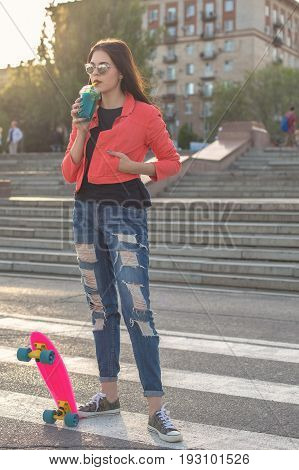 A teenage girl drinks fruit fresh. She has a skateboard. A hipster girl wearing sunglasses. Active way of life in urban space. Youth fashion.