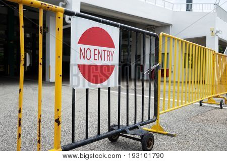sign of no entry on steel railing before building