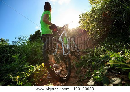 young woman cyclist with mountain bike climbing on summer forest trail