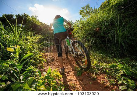 young woman cyclist carrying mountain bike climbing on summer forest trail