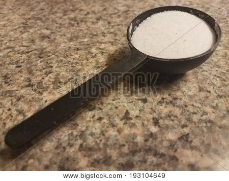 black plastic spoon filled with sugar on a kitchen counter