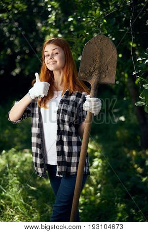 Young beautiful woman running in the garden, gardener, shovel.