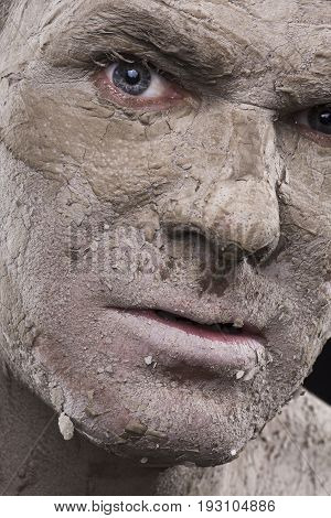Macro closeup scary face of man with dry flakes of cracked mud covering his skin like a mummified corpse
