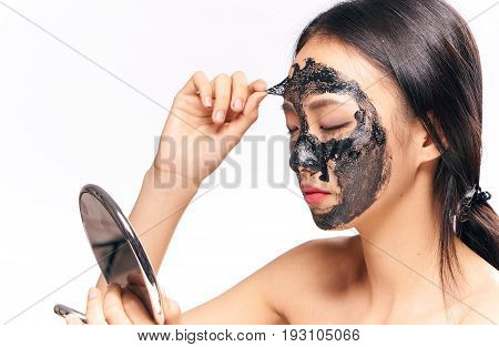 Asian woman on white isolated background, black coal cosmetic face mask.