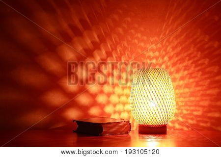 Nice wicker glowing desk lamp near old book against red wall