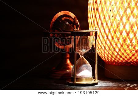 Vintage still life. Hourglass near old brass globe and glowing lamp on dark background