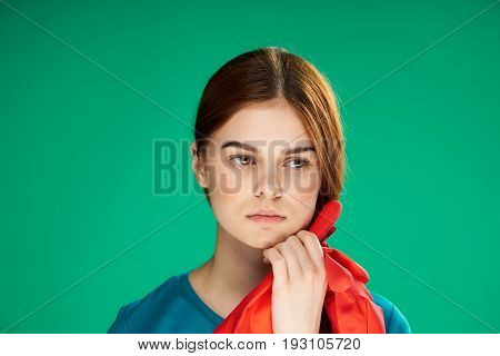 Woman with rubber gloves on a green background.