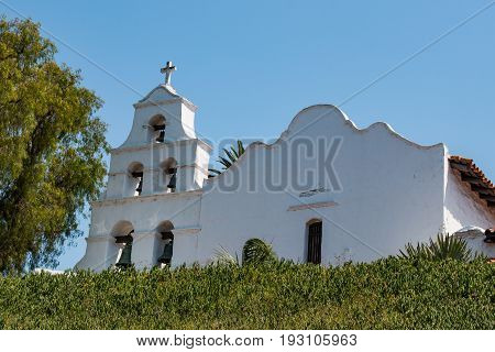 SAN DIEGO, CALIFORNIA - JUNE 24, 2017:  Church facade and bell tower of Mission Basilica San Diego de Alcala, the first Franciscan mission in The Californias, founded by Spanish friar Junipero Serra.