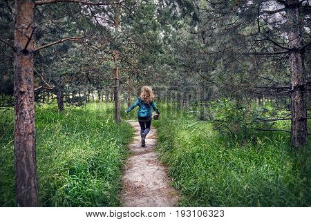 Young woman in green checked shirt with long hair running on the path in the pine forest with hat in her hand