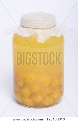 Queen palm fruits fermenting in glass jar making natural pro-biotic beverage on white background