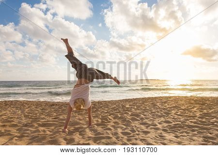 Relaxed woman enjoying sun, freedom and life turning cartwheel on beautiful beach in sunset. Young lady feeling free, relaxed and happy. Vacations, freedom, happiness, enjoyment and well being.