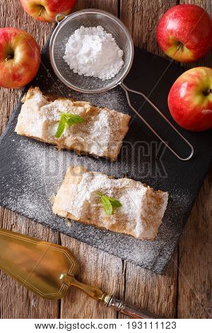 German Apple Strudel With Powdered Sugar And Mint Closeup On A Table. Vertical Top View