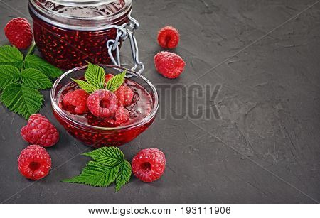 Close Up View Jam In Glass Jar And Bowl With Fresh Ripe Raspberry And Leaves