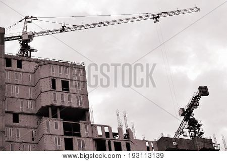 Working Tall Cranes Inside Place For With Tall Buildings Under Construction Against A Clear Blue Sky