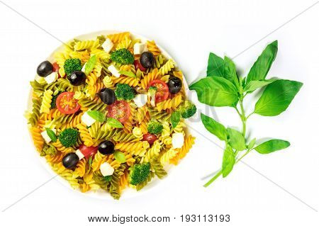 A photo of a plate of pasta salad with basil leaves, shot from above on a white background with a place for text