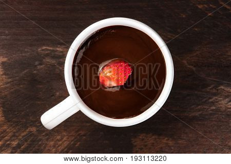 An overhead photo of a strawberry in a cup of dark chocolate, shot from above on a rustic wooden texture with a place for text