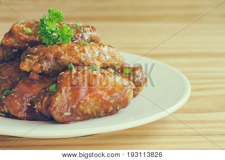 Barbecue chicken wings on white plate put on rustic wood table. Homemade barbecue chicken wing delicious moist and spicy. Barbecue chicken wing decorated with spice and parsley ready to served.