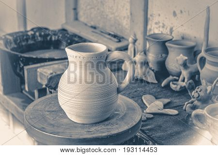 Old vintage photo. Clay jug on a potter's wheel close-up. Copy spase. Old vintage style.
