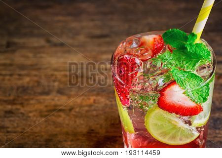 Strawberry lemon lime soda in clear glass on rustic wood table. Homemade strawberry soda ingredients with strawberry lemon or lime and mint leaf. Homemade infused water close up concept. Strawberry and lemon soda on plank with copy space.