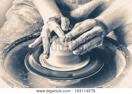 Potter hands creating a product from clay on a potter's wheel. Hands close-up master. Old vintage style.