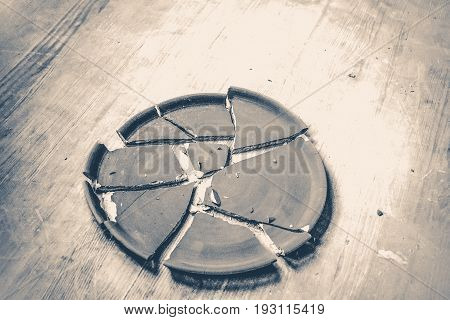 Broken clay plate lying on a wooden table. Old vintage style.