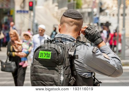 JERUSALEM, ISRAEL. June 20, 2017. Israel border police guard fixing earphone by the Damascus gate, the place of the recent terror attack. Israeli police soldier security stock image.