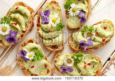 Canapes with avocado paste and edible flowers on wooden background