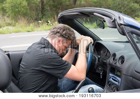 Man On The Side Of The Road With His Hands On Head Next To A Broken Down Car