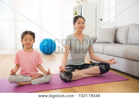 Mother With Children Meditating Doing Yoga