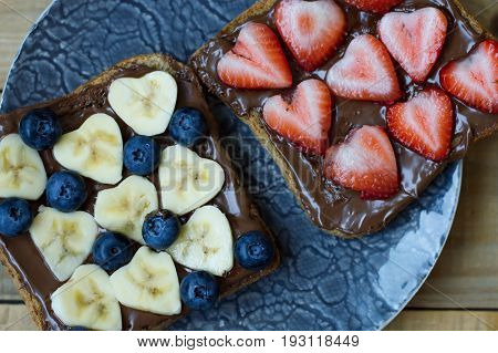 Two fruit sandwiches with banana strawberry blueberry chocolate spread and whole grain bread. Heart shaped banana and strawberry slices