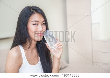 Woman drinking water in the bed room (water asian drink)