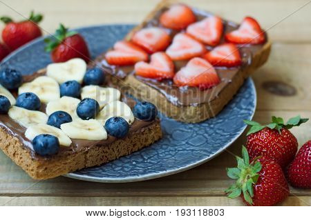Two sweet sandwiches with blueberry heart shaped banana and strawberry chocolate spread and whole grain bread. Breakfast food