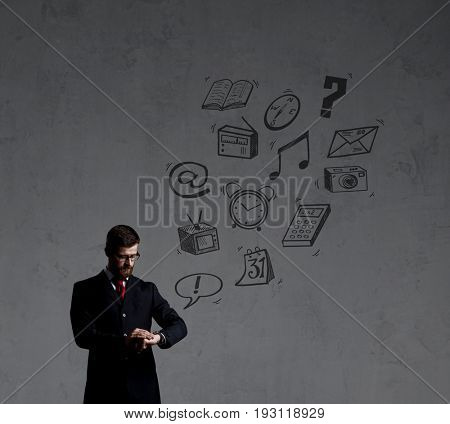 Businessman checking the time over dark dramatic background. Business and office, concept.