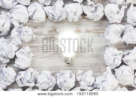 Many balls of crumpled paper and glowing light bulb
