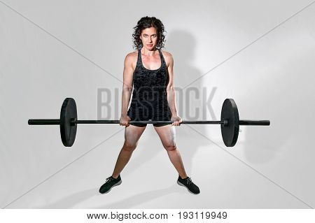 Tough female weightlifter holds a barbell in a dead lift with an intense glare for the camera. There is a path around the woman.